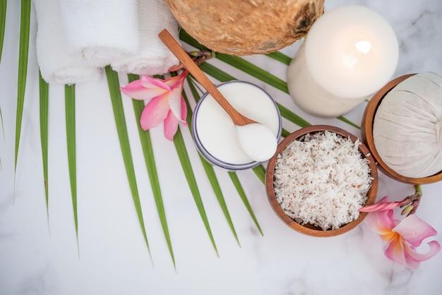 Olej kokosowy, tropikalne liście i świeże orzechy kokosowe. produkty kokosowe spa na jasnej powierzchni drewnianej.