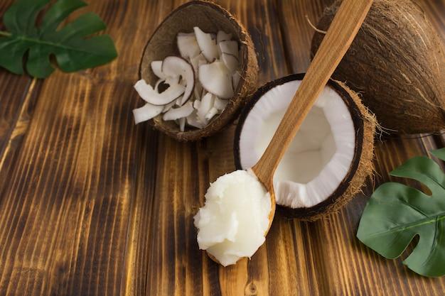 Olej kokosowy w drewnianej łyżce i chipsy kokosowe na brązowym drewnianym stole. naturalne produkty.