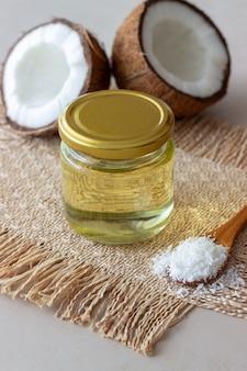 Olej kokosowy w słoiku i świeże orzechy kokosowe. kosmetyki naturalne.