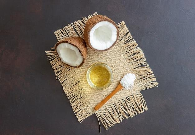 Olej kokosowy w słoiku i świeże orzechy kokosowe na ciemnej powierzchni. kosmetyki naturalne.