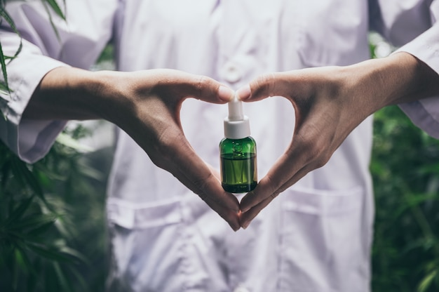 Olej konopny cbd, ręka trzymająca butelkę oleju konopnego