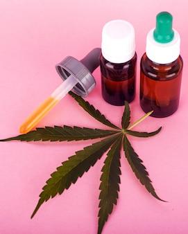 Olej konopny do użytku medycznego, butelki z wyciągiem z marihuany na różowym tle z bliska.