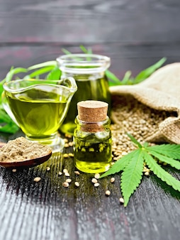 Olej konopny w dwóch szklanych słoikach i sosjerka ze zbożem w worku, łyżką z mąką, liśćmi i łodygami konopi