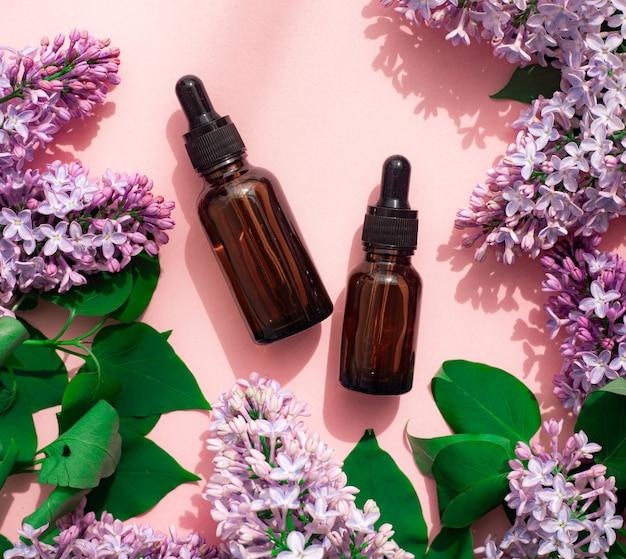 Olej kosmetyczny i liliowy na różowym tle. pojemnik na olejek kosmetyczny. kosmetyka. ochrona skóry .