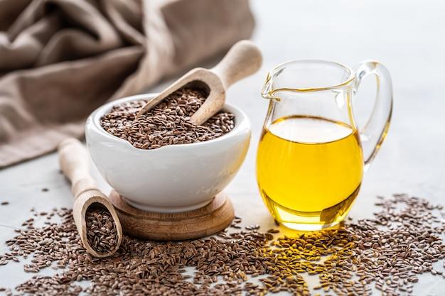 Olej lniany w butelce i ceramicznej misce z brązowymi nasionami lnu i drewnianą łyżką na białym