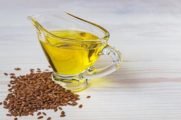 Olej lniany w łodzi sos szklanej, nasiona lnu na białym tle.