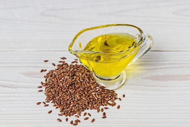 Olej lniany w szklanej łodzi z sosem i nasiona lnu na białej powierzchni