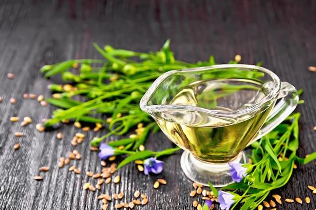 Olej lniany w szklanej łodzi z sosem z nasion, liści i kwiatów lnu na ciemnym tle deska