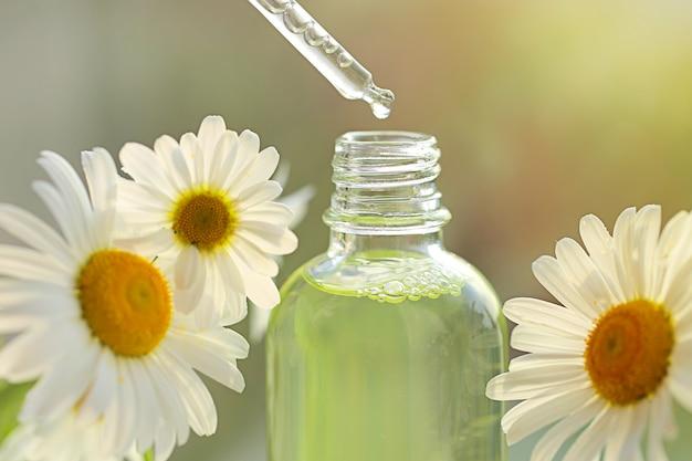 Olej rumiankowy. olej w przezroczystej butelce z pipetą i kwiatami rumianku