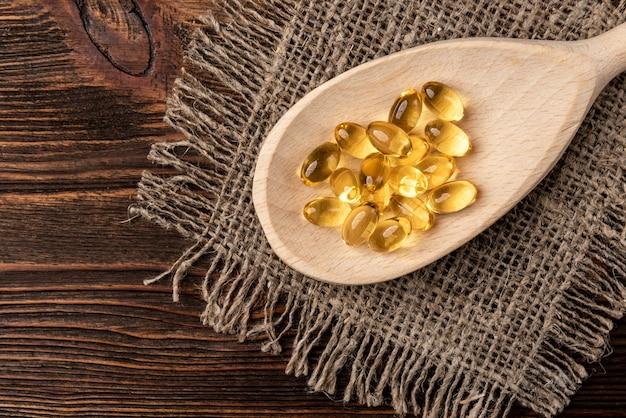Olej rybny na ciemnym drewnianym stole.