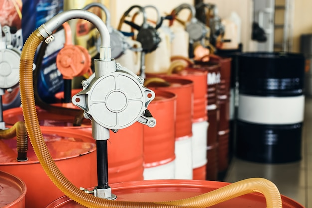 Olej silnikowy w beczkach z pompą w pomieszczeniu z miejscem na kopię. przechowuj smar. produkt do rozlewania z bliska. konserwacja. magazyn w środku.