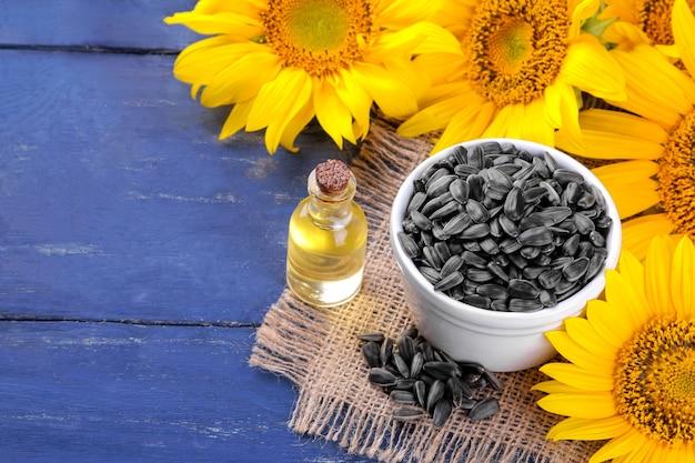 Olej słonecznikowy i nasiona słonecznika z pięknymi żółtymi słonecznikami w tle na niebieskim drewnianym tle