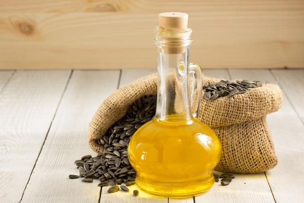 Olej słonecznikowy i ziarna na drewnie