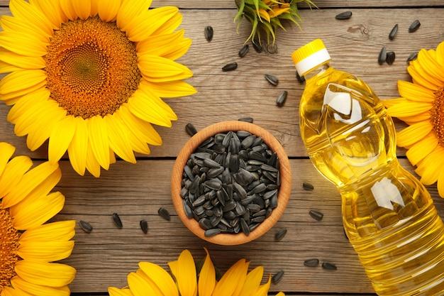Olej słonecznikowy, nasiona i słonecznik na szarym drewnianym tle