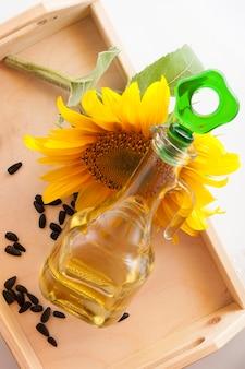 Olej słonecznikowy w przezroczystym dzbanku z kwiatem słonecznika