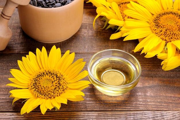 Olej słonecznikowy w szklanej misce obok żółtych jasnych słoneczników na brązowym drewnianym tle