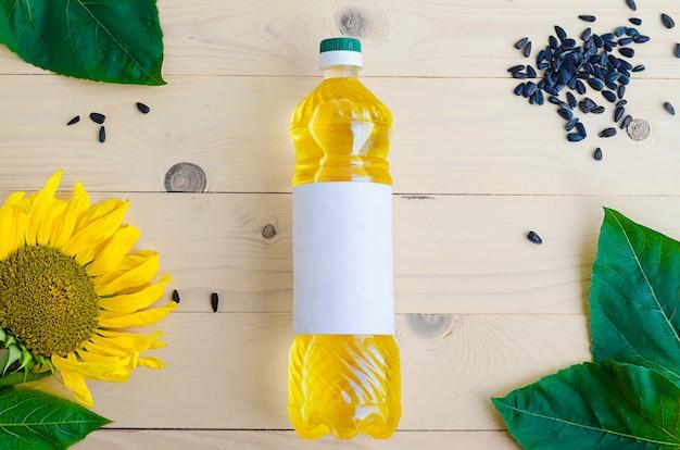 Olej słonecznikowy z kwiatem i nasionami w butelce.