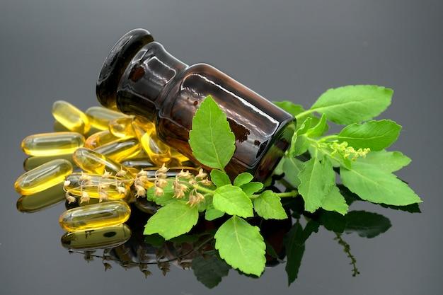 Olej w kapsułce, butelce z bursztynu i świeżych ziół na ciemnym tle.