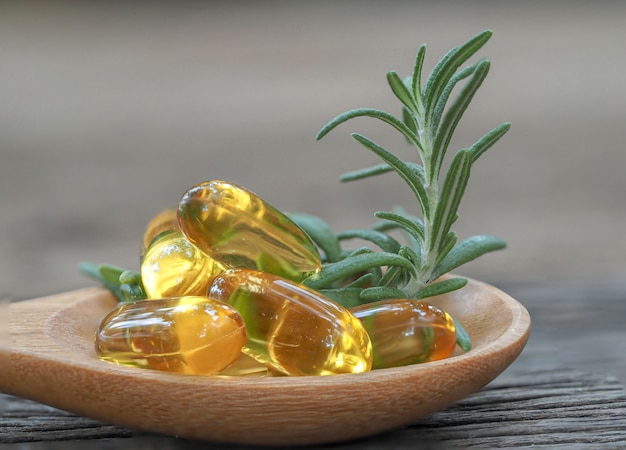 Olej w kapsułkach rozmarynowy ze świeżym rozmarynem na stole z drewna, koncepcja zdrowego oleju ziołowego