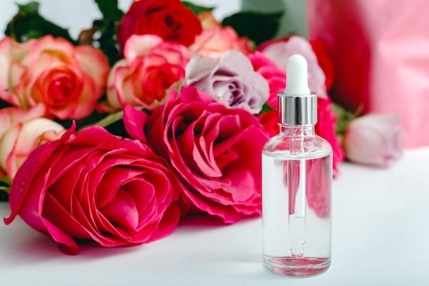 Olej w surowicy na tle kwiatów biały stół. kwiat czerwony różowy róż naturalny organiczny produkt kosmetyczny. spa, pielęgnacja skóry, kąpiele na ciało. szklana butelka kosmetyczna z różą makieta.
