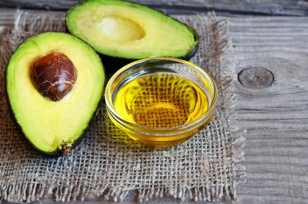 Olej z awokado w szklanej misce i świeżym organicznym awokado