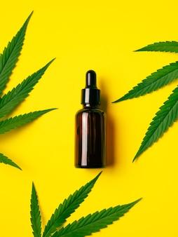 Olej z konopi indyjskich w butelce z zakraplaczem z zielonymi liśćmi na żółtym tle. koncepcja medycyny alternatywnej.