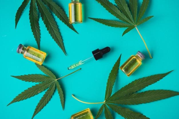 Olej z konopi indyjskich w butelkach z zakraplaczem z zielonymi liśćmi na zielonym tle. koncepcja medycyny alternatywnej.