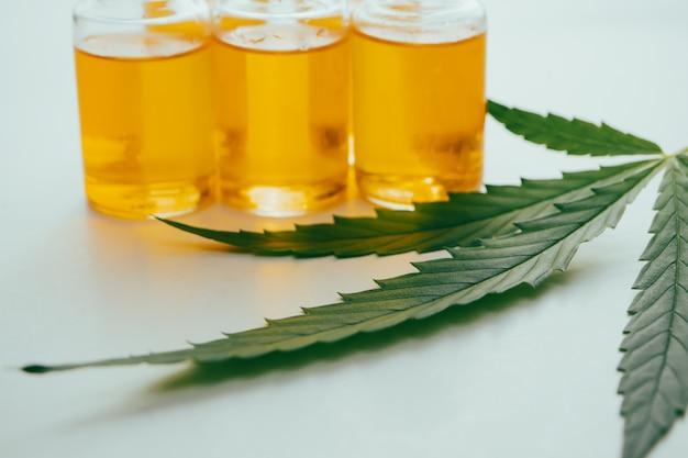 Olej z konopi indyjskich w fiolkach z zielonym liściem na białym tle. koncepcja medycyny alternatywnej.