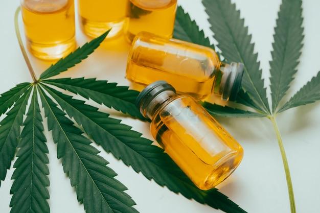 Olej z konopi indyjskich w fiolkach z zielonymi liśćmi na białym tle. koncepcja medycyny alternatywnej.