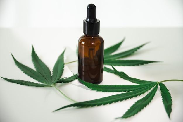 Olej z konopi w butelce z zakraplaczem z zielonymi liśćmi. koncepcja medycyny alternatywnej.