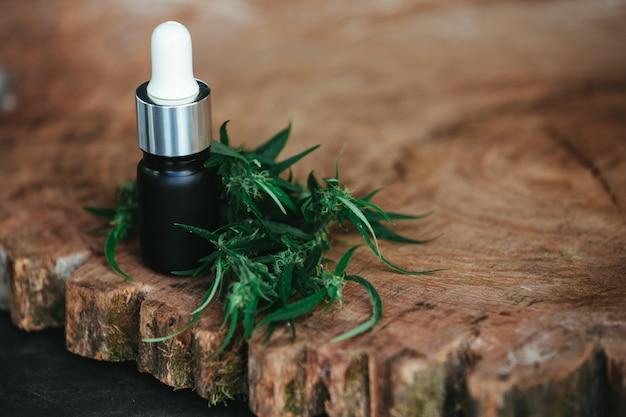 Olej z konopi w połączeniu z konopiami na brązowej drewnianej podłodze.