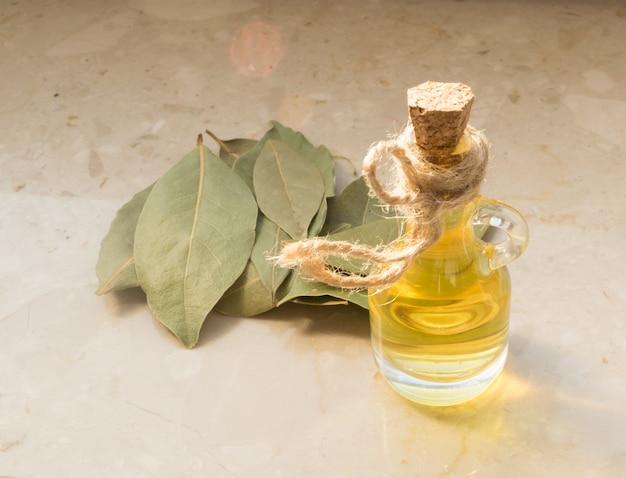 Olej z liści laurowych na tle beżowego marmuru. laurel essential z naturalnym światłem słonecznym
