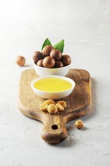 Olej z orzechów makadamia w białej misce na drewnianej desce do krojenia.