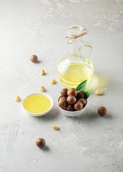 Olej z orzechów makadamia w butelce i misce na betonowym tle.