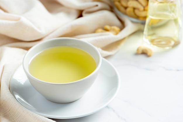 Olej z orzechów nerkowca z orzechami nerkowca na marmurowym tle
