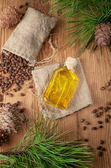 Olej z orzeszków piniowych. na drewnianym tle. w pobliżu orzeszki pinii i szyszki. widok z góry.