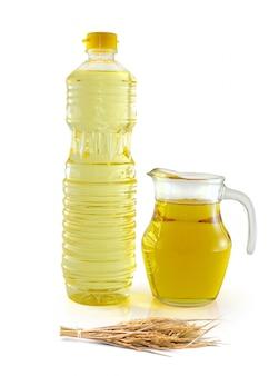 Olej z otrębów ryżowych w szklance butelki z nasionami i otrębami na białym tle