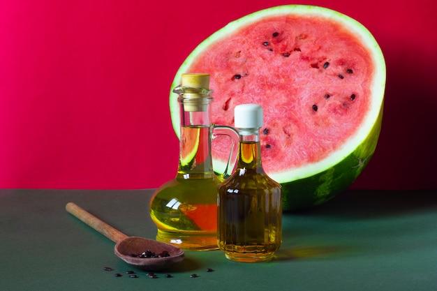 Olej z pestek arbuza w szklanym słoiku, surowe nasiona i duży arbuz na czerwonym i zielonym tle
