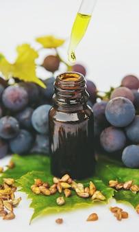 Olej z pestek winogron w małej butelce. selektywne ustawianie ostrości.