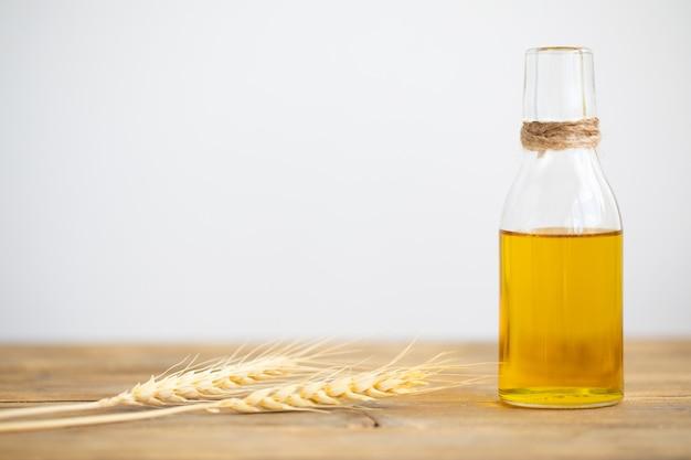 Olej z pszenicy w butelce i kłosy pszenicy na drewnianym stole na białym tle. skopiuj miejsce.