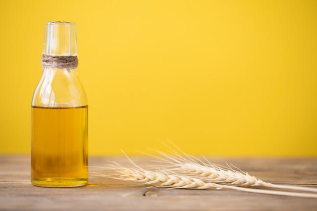 Olej z pszenicy w butelce i kłosy pszenicy na drewnianym stole na żółtym tle. skopiuj miejsce.