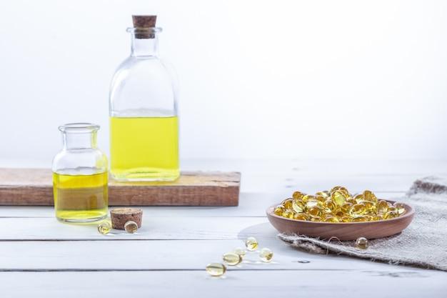 Olej z wiesiołka w kapsułkach i butelkach, na białej drewnianej podstawie. pojęcie opieki zdrowotnej.
