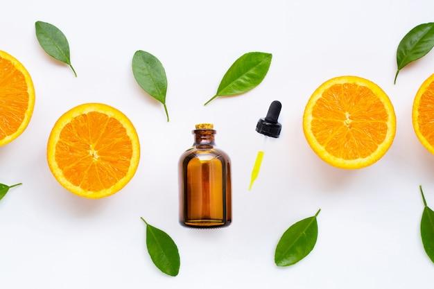 Olejek cytrusowy ze świeżymi pomarańczowymi owocami na białym tle