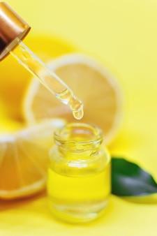 Olejek cytrynowy na żółtym tle. selektywne skupienie.