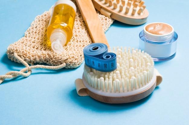 Olejek do ciała, miarka, dzianinowa myjka, naturalny domowy peeling w słoiczku i szczotka do masażu na sucho na niebieskiej powierzchni