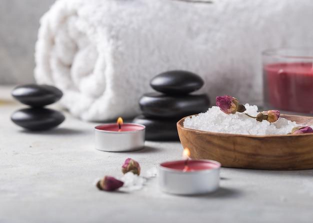 Olejek do masażu butelka aromatycznej i naturalnej soli zapachowej z kamieniami, świece na betonowym szarym stole.