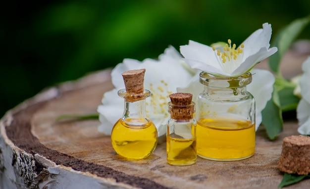 Olejek eteryczny i kwiaty jaśminu na drewnianym tle. zabiegi kosmetyczne. selektywne skupienie
