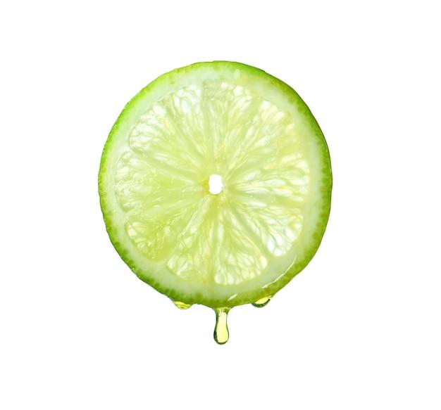 Olejek eteryczny kapie z plasterka limonki na białej powierzchni