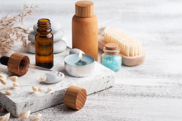 Olejek eteryczny w butelkach wielokrotnego użytku na podłoże drewniane. naturalne organiczne spa z ekologicznym opakowaniem