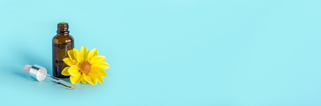 Olejek eteryczny w otwartej brązowej butelce z zakraplaczem i żółtym kwiatem na niebieskim tle. koncepcja produktu kosmetycznego